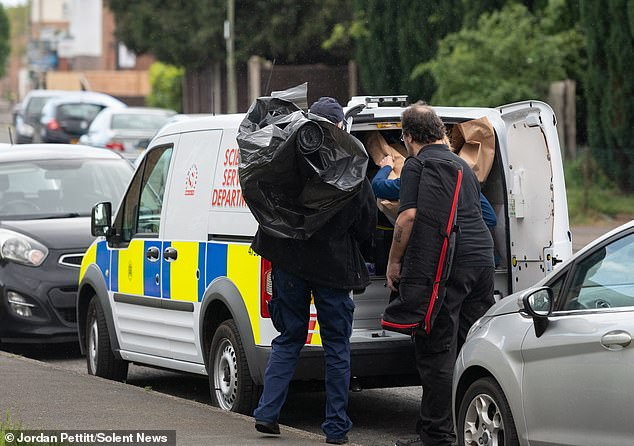 Investigating Special Forensic Service officers were seen putting items into a marked police van parked outside