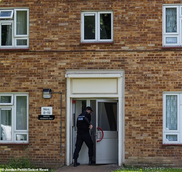 A police officer enters the property in Leigh Park after a body was found in woodlands