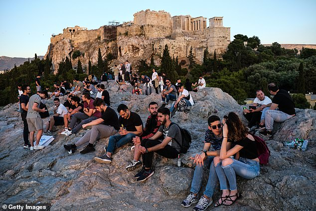 Tourists and local Athenians watch the sunset on Areopagus Hill, with the Acropolis in the background, on May 23,