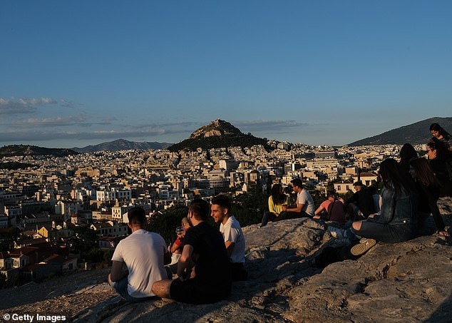 Tourists and local Athenians watch the sunset on Areopagus Hill, with the Lycabettus Hill in the background, on May 23