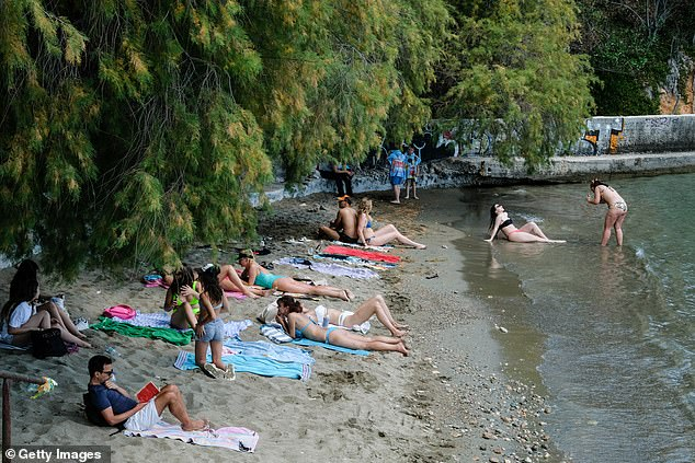 People enjoy a day at the beach on May 23.Greek authorities say they have performed 152,998 tests for the disease
