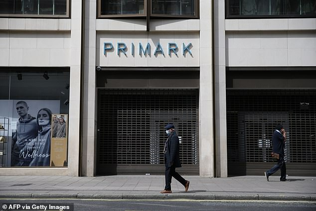 A man wearing a face mask walks past a closed Primark store in Oxford Street in central London on May 14