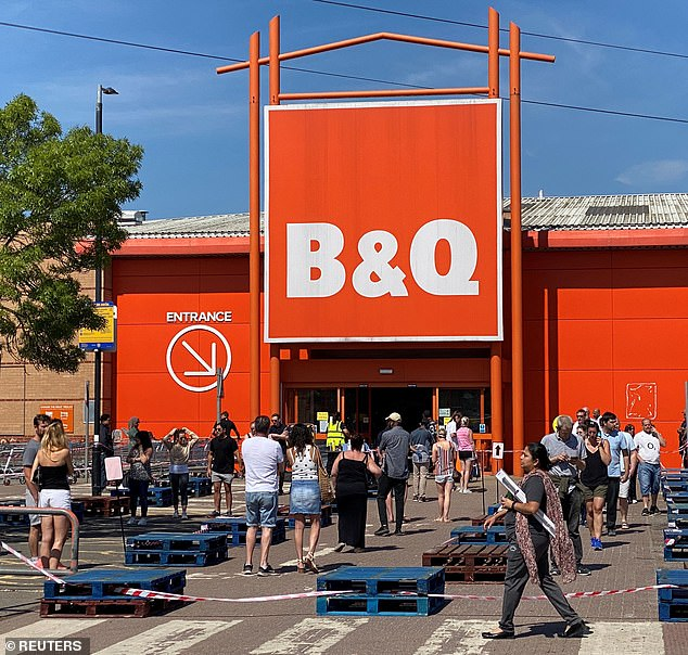 People queue outside a B&Q DIY store in Watford following the outbreak of coronavirus