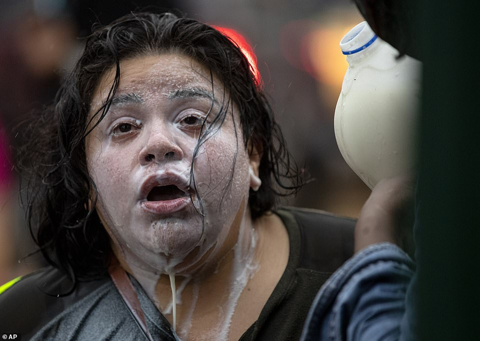 Demonstrators carrying placards reading 'I can't breathe' and 'Justice 4 Floyd' surrounded a police precinct Tuesday night. Milk drains from the face of a protester who had been exposed to percussion grenades and tear gas outside the Minneapolis Police 3rd Precinct on Tuesday