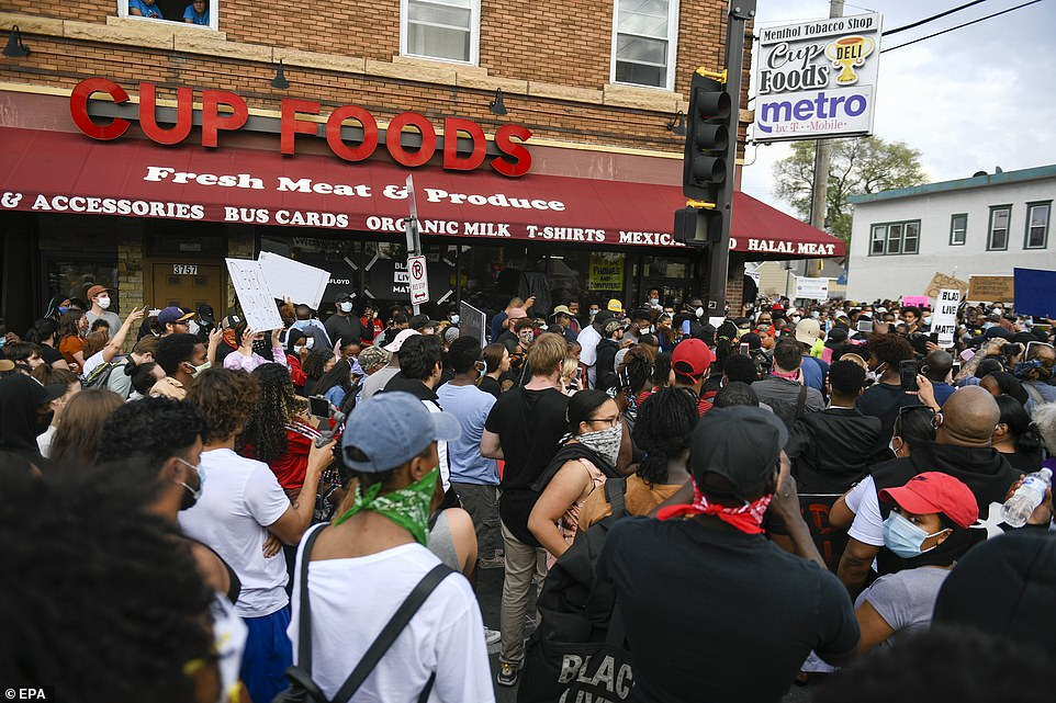 Protesters gather outside the Cup Foods store where Floyd was detained by a white cop on Monday when the officer pinned him down by his neck in the street