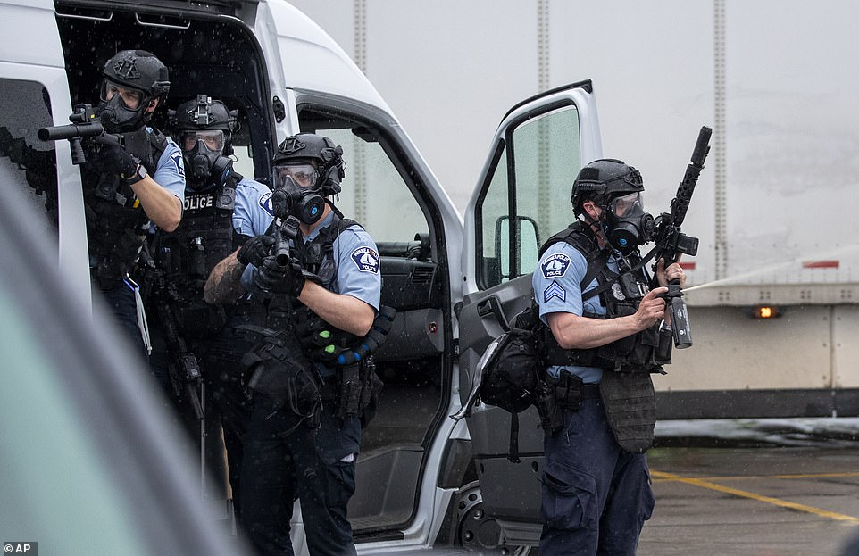 Police are pictured in riot gear at the rally. The protest in the streets of Minneapolis over his death descended into chaos Tuesday night