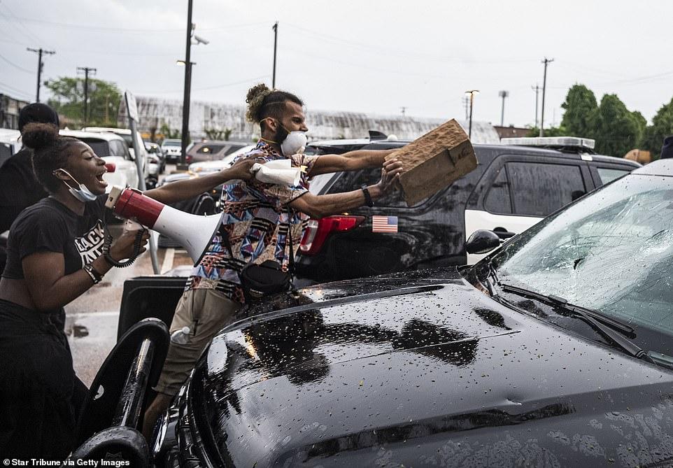 A protester throws a brick onto an empty squad car near the Minneapolis 3rd Police Precinct Tuesday night