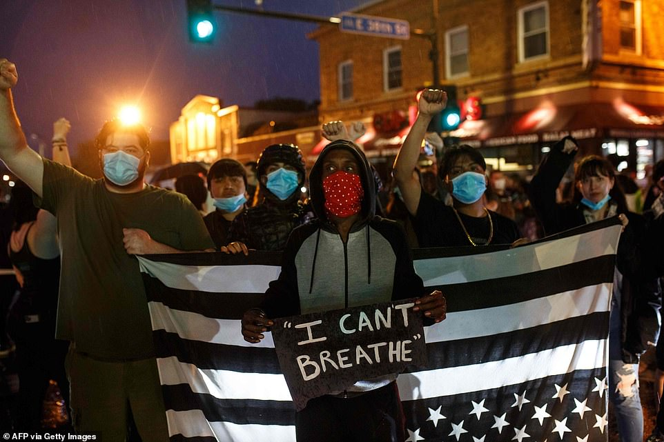 Protesters raised their fists and sported face masks to protect them from the spread of COVID-19 as they gathered for the rally near the spot where Floyd died