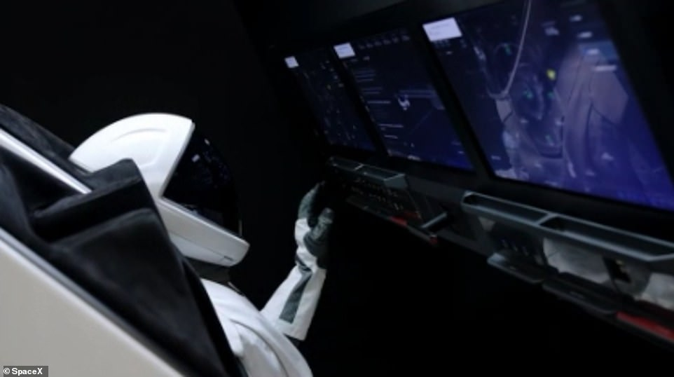 One of the astronauts training and using an ISS docking simulator with the touch screen control system used in the Crew Dragon capsule