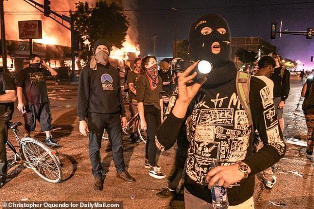 Some rioters had their faces covered with balaclavas, masks and cloths as they watched fires rage around them