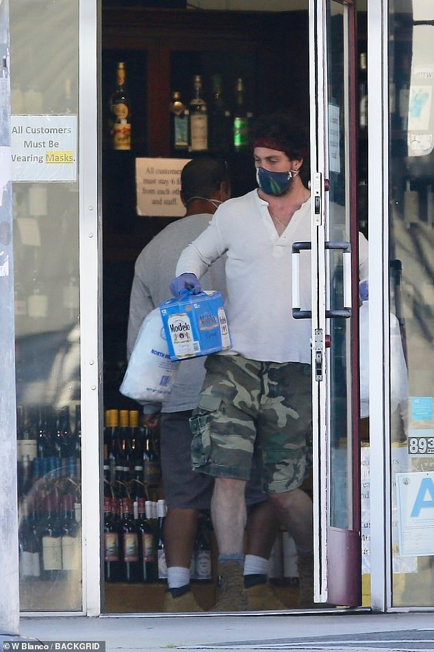 Stocking up: The actor, 29, was cautious in a face mask and gloves as he bought beer and ice from the store
