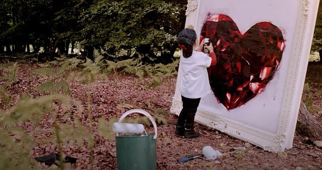 Cute: The video shows Ronan finding his son Cooper painting an enormous heart in the woods in honour of NHS staff