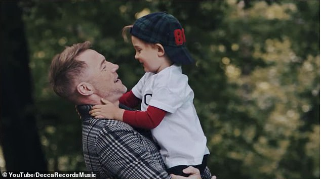 Sweet: The cute video also featured a surprise appearance from the singer's son Cooper, 3, painting an image in the woods in honour of NHS staff