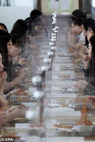 Students eat lunch at tables equipped with plastic barriers in Doan High School in Daejeon, South Korea, 20 May 2020