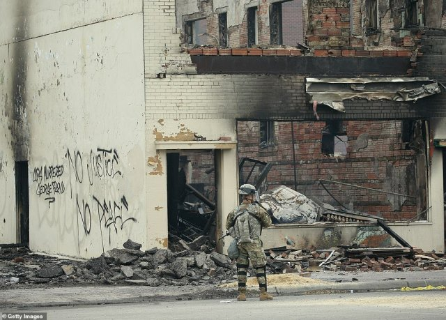 A member of the National Guard patrols near a burned out building on the fourth day of protests in Minneapolis
