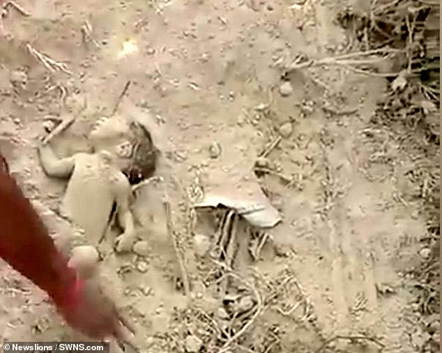 Infant's small body is freed of dust while rescuers try to see if he is alive