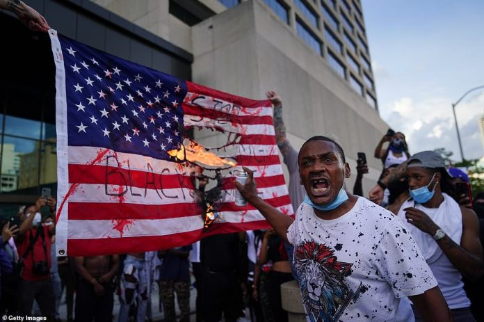 Atlanta:Protesters burn an American flag outside the CNN Center on Friday