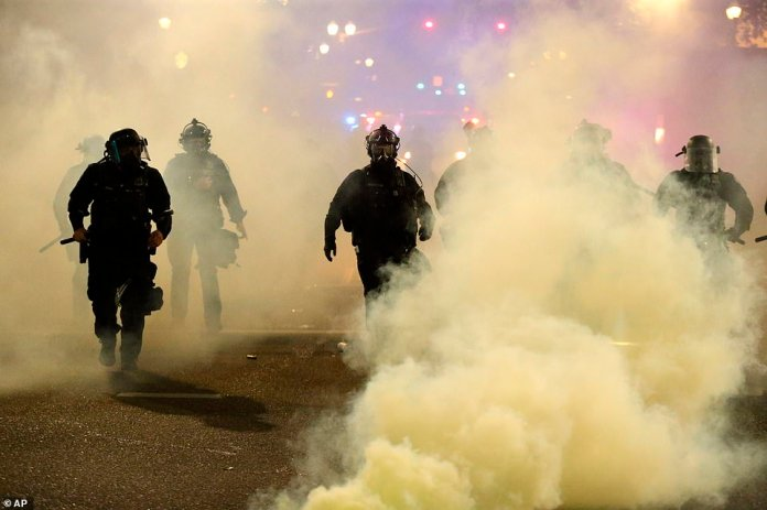 Portland: Policemen walk enveloped by teargas in Portland, Oregon, yesterday as violence escalated in the downtown area