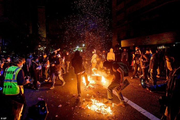 Demonstrators burn items in Oakland, California, yesterday while protesting the death of George Floyd