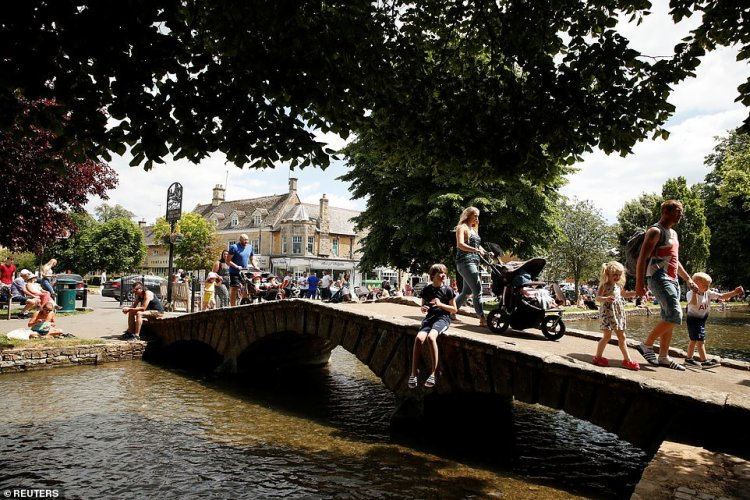 Bourton-on-the-Water in the Cotswolds is packed with visitors this afternoon as families visit the banks of its river