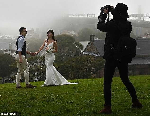 In Queensland, Victoria and New South Wales, couples can now have up to 20 guests at their weddings. (Pictured: A couple at Observatory Hill, Sydney, on May 19)