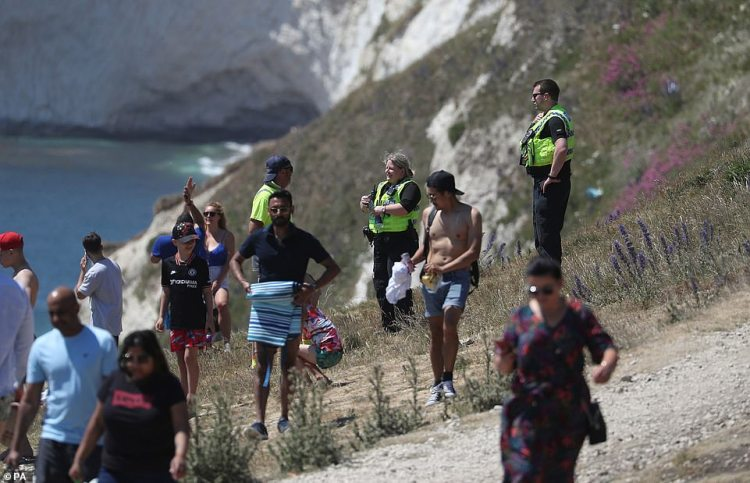 Police patrol the cliff top near Durdle Door, Lulworth, after Dorset Council announced that the beach was closed to the public after three people were seriously injured jumping off cliffs into the sea