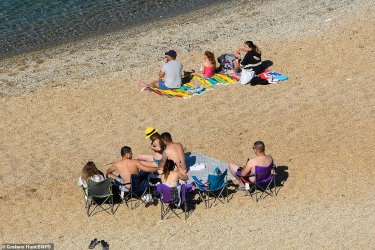 Visitors begin to arrive at the beach at Durdle Door at Lulworth in Dorset at the start of another day of scorching hot sunshine