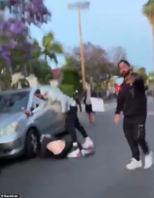 Smith was filmed in a gray hoodie and black pants kicking the protester on the ground at least four times for allegedly vandalizing his truck