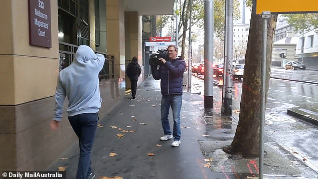 A television cameraman films a friend of Rian Farrell outside a Melbourne court. The cameraman was attacked seconds later