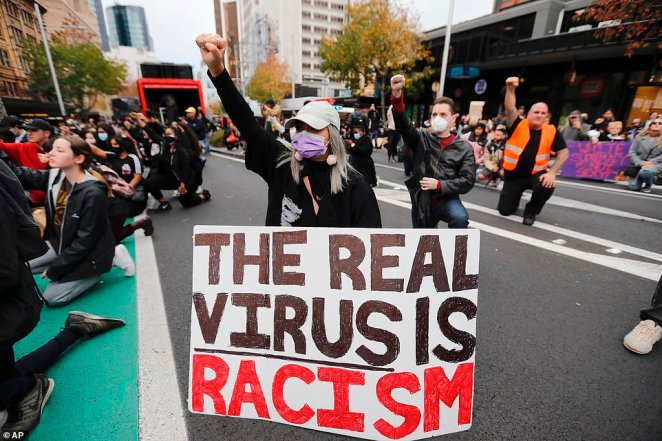 Protesters dropped to their knees and raised a fist outside the US embassy in Auckland in protest of the death of George Floyd