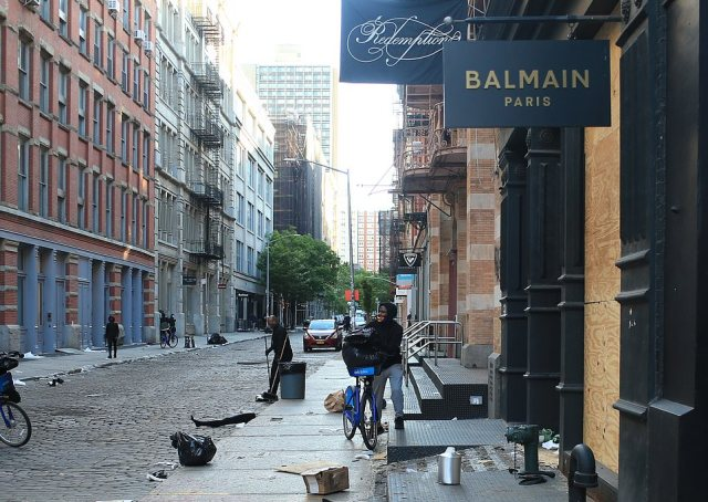 Street cleaners on Monday morning in Soho. There were still boxes of goods strewn in the street from the stores