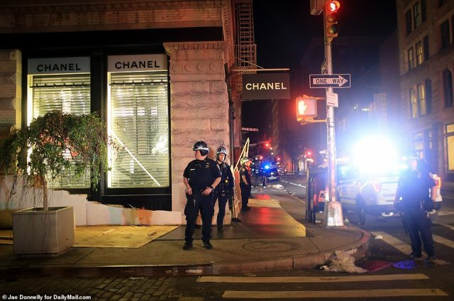 NYPD officers in Soho on Sunday night after the looters tore down plywood at Chanel