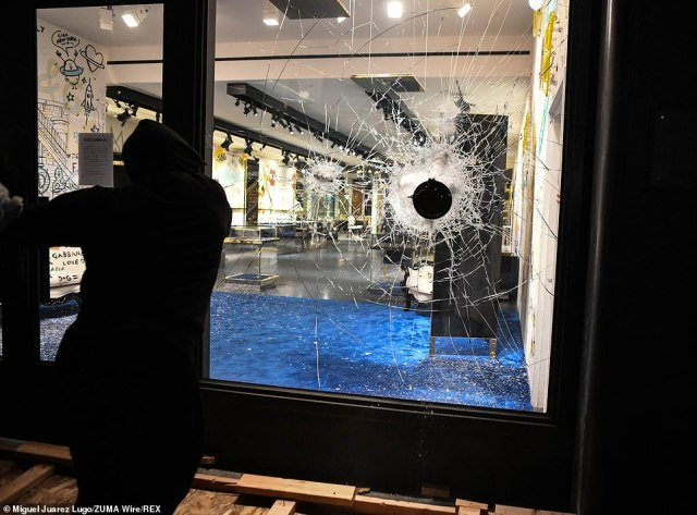 A looter smashes the window at Dolce and Gabanna on Sunday night in New York's Soho