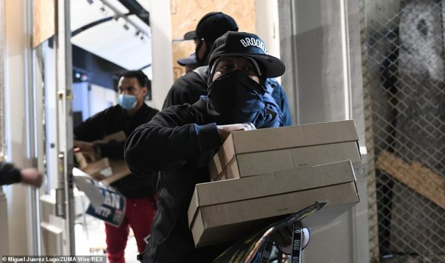 Looters taking from a store in Soho on Sunday night before police arrived