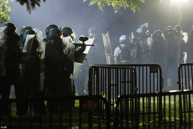 Police armed with plastic shields, bulletproof vests, and weapons pictured at Lafayette Park as demonstrators gathered for the sixth night on Sunday evening