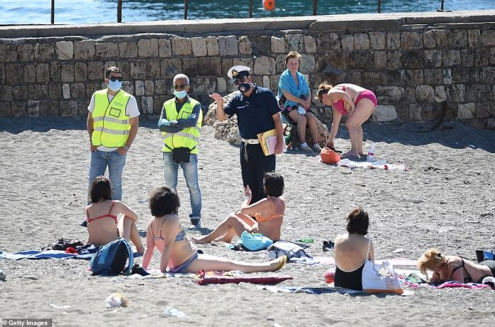 A police officer talks to beach goers in Italy. UK has more cases of coronavirus per million people than most of the 15 most popular holiday destinations for Britons - including Italy