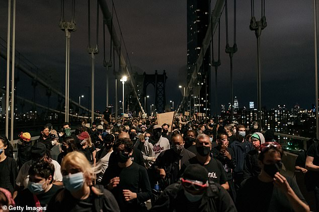 Protesters leave the Manhattan Bridge on June 2 after being stopped by police during an 8pm curfew which thousands ignored but which was followed by less rampant destruction than on previous days in New York City