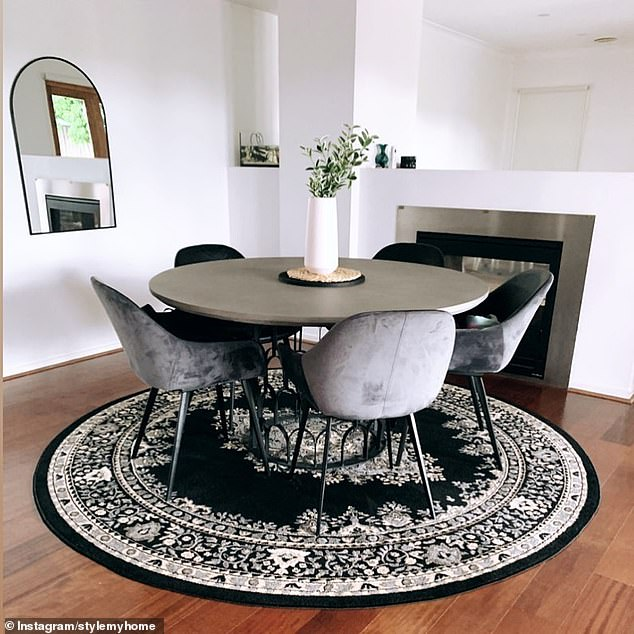 In the living room a circular black mosaic rug sits underneath a silver table, with velvet silver chairs to match the silver-framed fireplace in the background (pictured)
