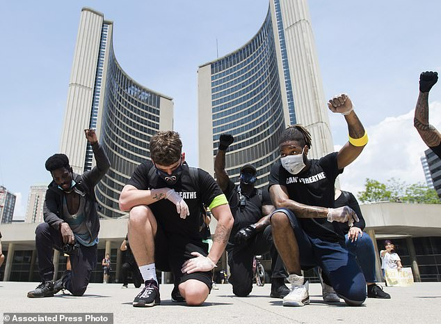 Protesters raise their fists at an anti-racism demonstration, in Toronto on Friday, June 5