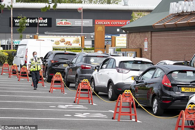 LIVINGSTON: Security walks along a line of cars lining up at a McDonald's in Livingston, Scotland