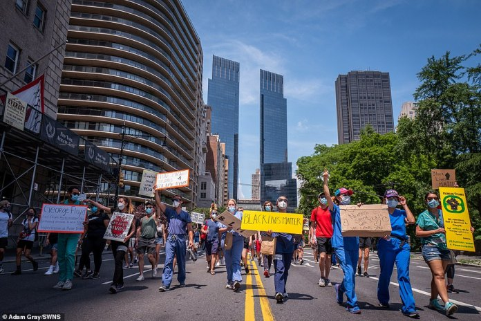 NEW YORK CITY: Healthcare workers with Frontline4Change demonstrate alongside audience in Manhattan on Saturday holding placards stating 'Black Lives Matter' and 'Nurses Stand With You'