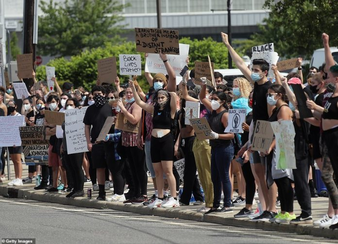 BETHPAGE, NEW YORK: Protesters hold signs in support of the Black Lives Matter Movement at Bethpage on Saturday. The group was joined by counter-protesters who were standing a block away but were in much smaller numbers