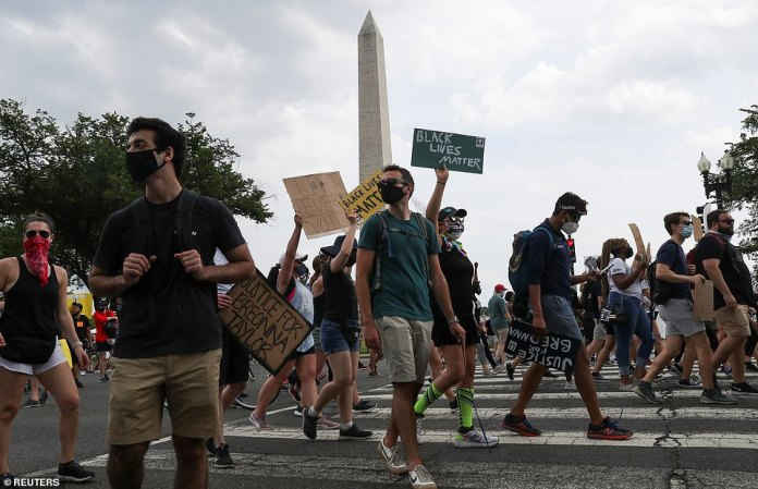 Protesters march in front of the Washington Monument near the White House