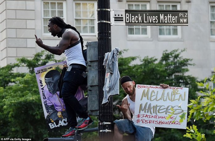 Activists and protesters gathered at the Capitol, on the National Mall and in many residential areas. Above, protester Mike D 'Angelo (left) stands atop a street sign that has been renamed' Black Lives Matter Plaza '