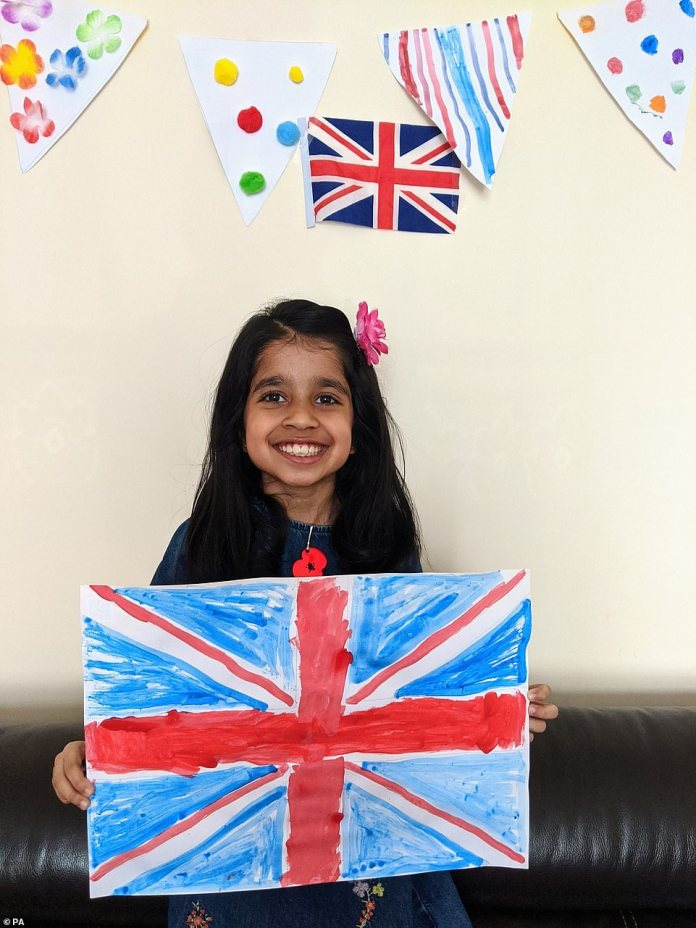 A schoolgirl flashes a beautiful smile as she brandishes a Union Jack design in a photo titled 'VE Celebration During Lockdown' by Vanita Bhuva