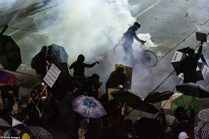The use of tear gas was banned for at least 30 days from Friday, but cops were seen again launching protesters on Sunday evening (above)