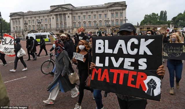 Activists, some wearing face coverings or face masks as a precautionary measure against COVID-19, hold placards as they attend a Black Lives Matter protest march as it passes in front of Buckingham Palace today