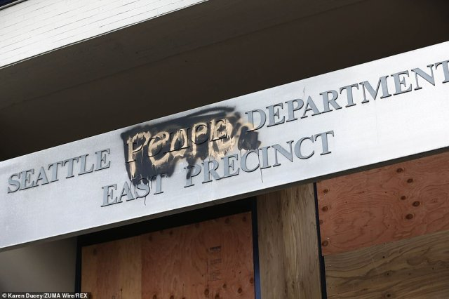A defaced sign is seen over the East Precinct in Seattle, which was abandoned by police on Monday
