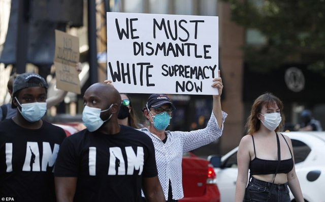 A woman holds a sign which reads 'We must dismantle white supremacy now' during a demonstration in Atlanta on Saturday