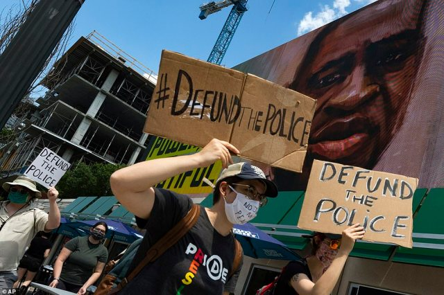 Protesters hold signs which read 'Defund the police' as they walk past a mural of George Floyd in Atlanta on Saturday